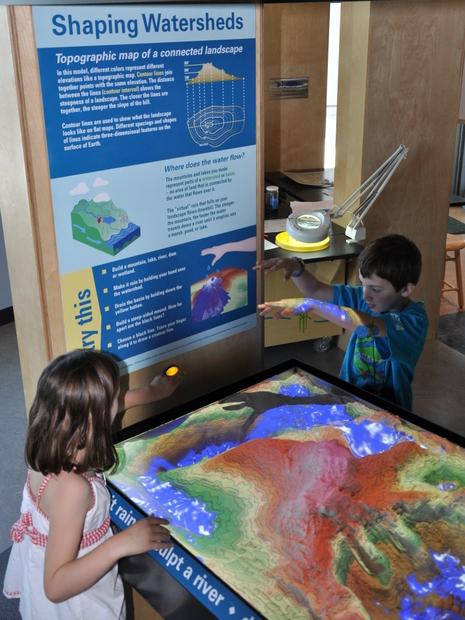 "Children ""make it rain"" over an augmented reality sandbox created by UC Davis researchers at ECHO Lake Aquarium in Vermont. Photo credit: Julie Silverman/ECHO Lake Aquarium. Copyright © The Regents of the University of California, Davis."