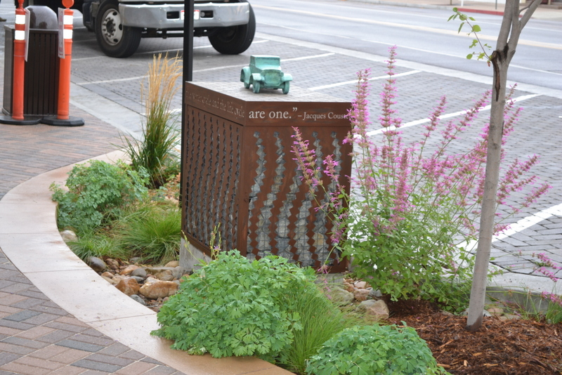 This rain garden and interlocking paver pilot on the Mitchell block in Old Town Fort Collins features a decorative testing box that houses a sampler. With this setup, the city tests runoff that has infiltrated the pavement.  Photo credit: City of Fort Collins
