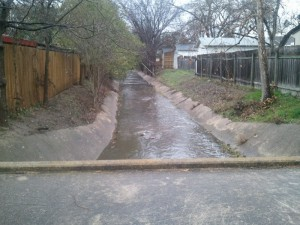 The City of Austin monitors waterways affected by a variety of land uses, including this cement-lined channel in a residential neighborhood. Image credit: COA-WPD-WQM