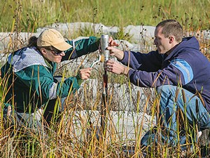 Utah State University students Margie Rycewicz-Borecki and Andrew Lewis prepare a soil sample at the bioretention site constructed for stormwater quality research. The team is working to determine if plants can play a more active role in remediating heavy metal buildup in stormwater retention areas. Image by Utah State