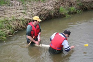 Soil experts David Lobb and Sheng Li check sediment collection traps. The sediment is collected annually to track the origin and pattern of soil migration. Image credit Landice Yestrau.