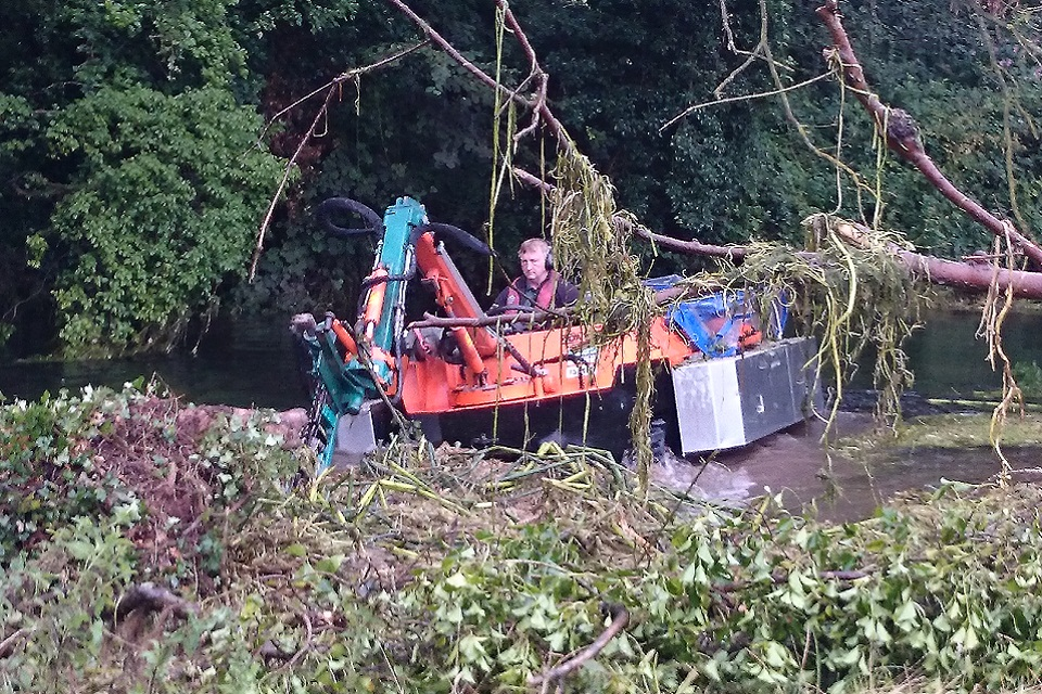 The Amphibious weed cutting boat in action. Image from the UK Environment Agency